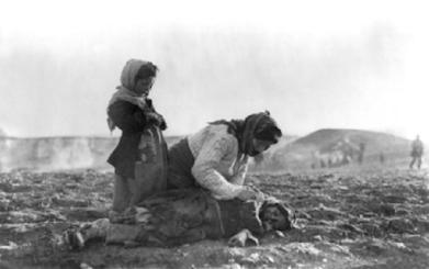 Uma mulher armênia se ajoelha ao lado do corpo de seu filho